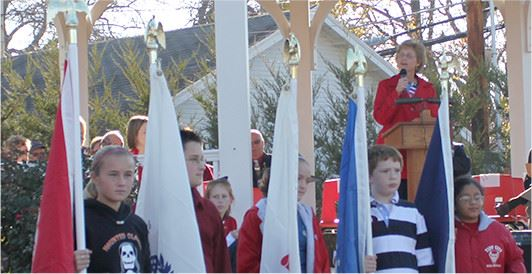 Young students holding flags at Veterans Day program